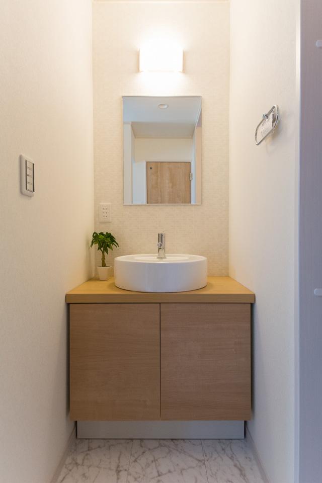 お洒落な丸型洗面器の手洗いキャビネットを玄関脇に設置。