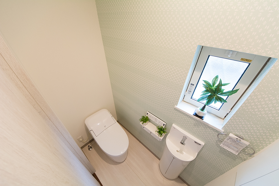 白を基調とした清潔感のある1階トイレ。ライトグリーンのアクセントクロスが爽やかな印象をプラス。