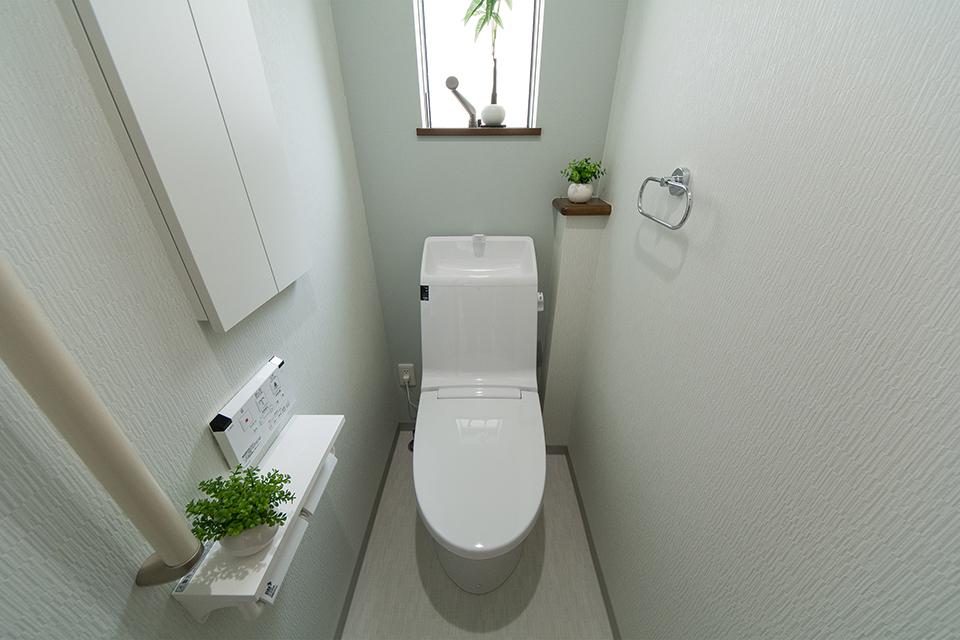 白を基調とした清潔感のある1階トイレ。ミントグリーンのアクセントクロスが爽やかな印象を。