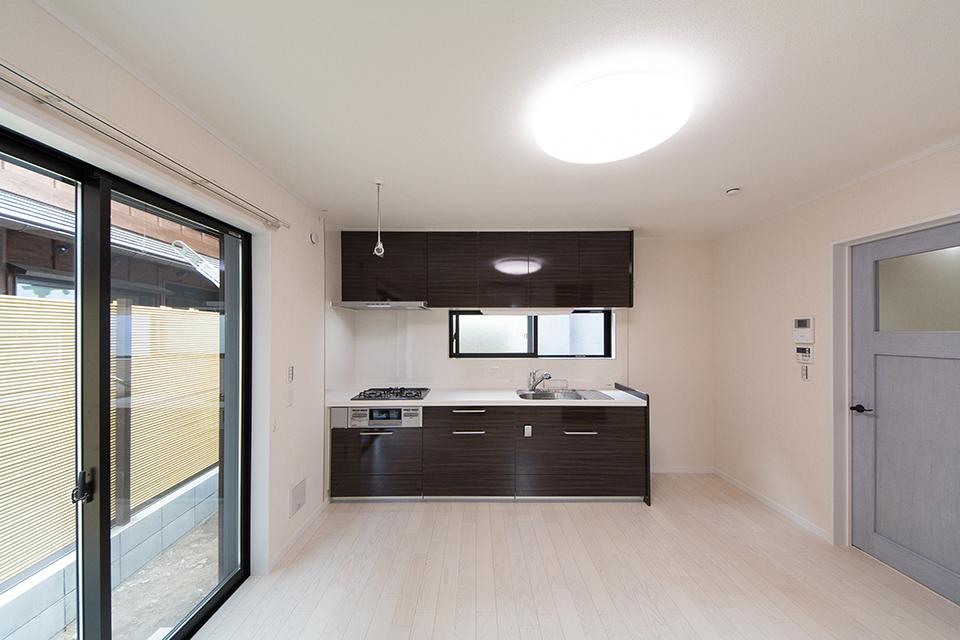 1階ダイニングキッチン。美しく繊細な木目のフローリング(ホワイトアッシュ)が窓から差し込む光を反射し、空間を優しく包み込みます。