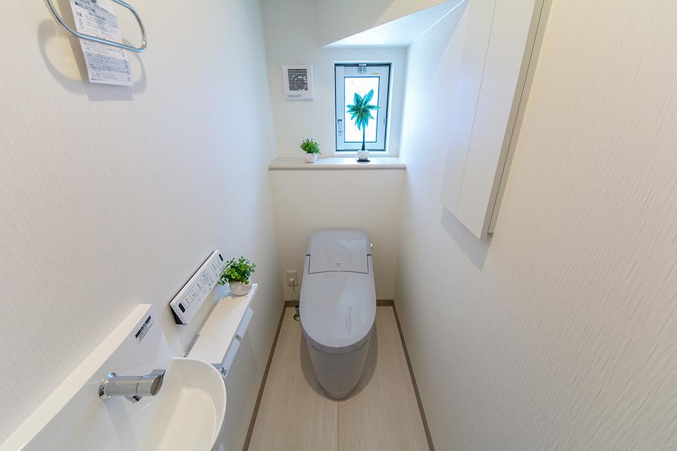 白を基調とした空間に、爽やかな印象を与えるブルーグレーのトイレを設えた1階トイレ。