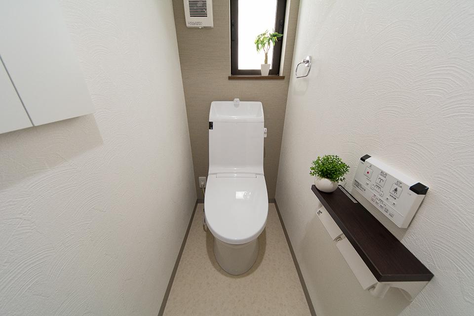 白を基調とした清潔感のある1階トイレ。背面のアクセントクロスが落ち着いた雰囲気を演出。