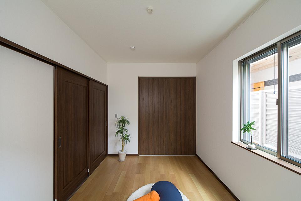 1階洋室。バーチのフローリングとウォルナットの建具が、リビング同様ナチュラルな空間を演出。