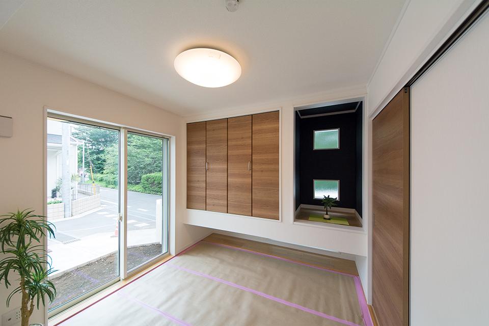 1階畳敷き洋室(写真は畳設置前)。紺色のアクセントクロスが空間を引き締め、モダンな雰囲気を演出。
