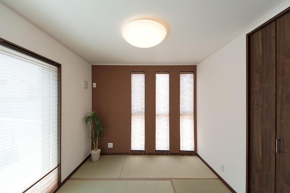 小豆色のアクセントクロスが空間を彩る畳敷き洋室。