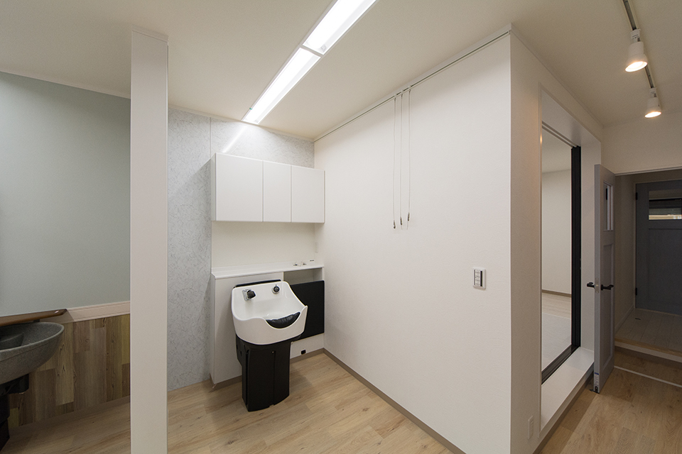 店舗部分(竣工時)白を基調とした清潔感のある洗髪スペース。