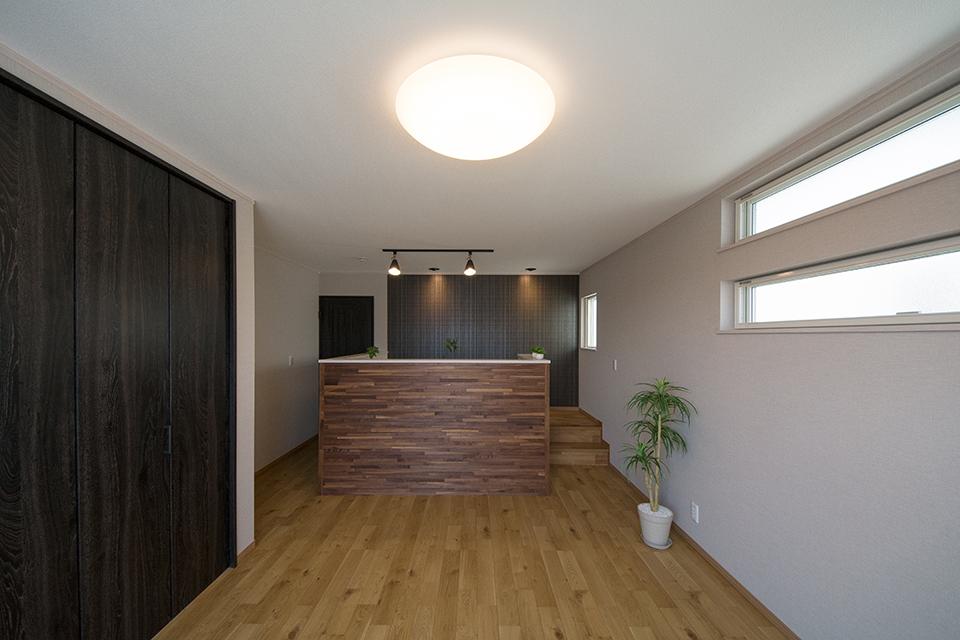 アッシュのフローリングとスモークオークの建具がナチュラルな空間を演出する2階洋室。
