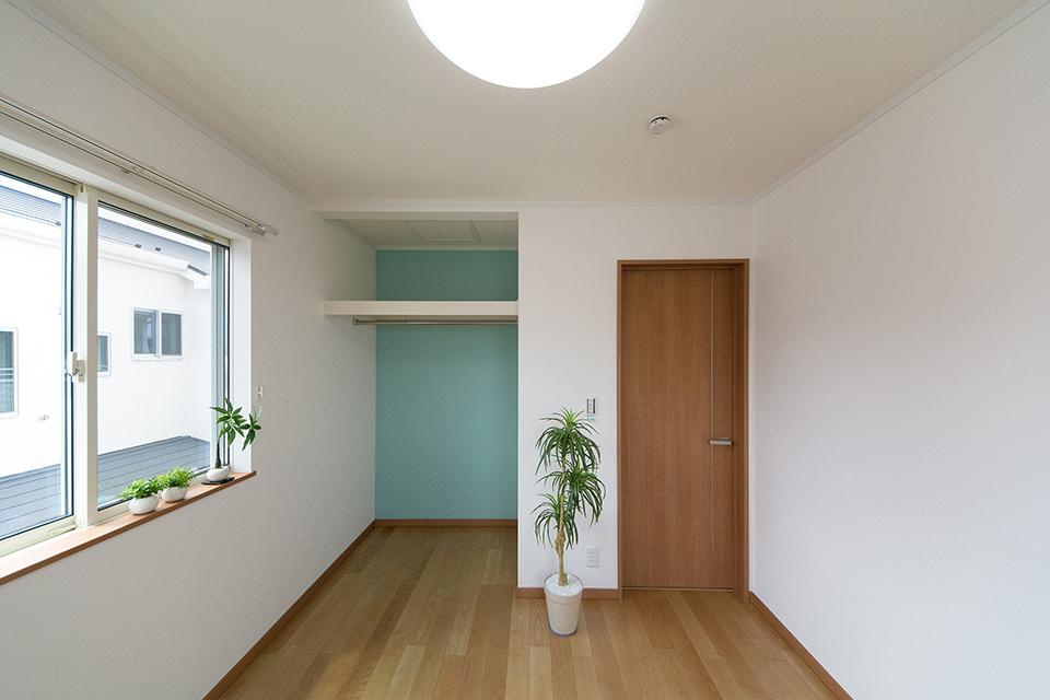 2階洋室。収納部分のエメラルドブルーのアクセントクロスが彩りある室内を演出。