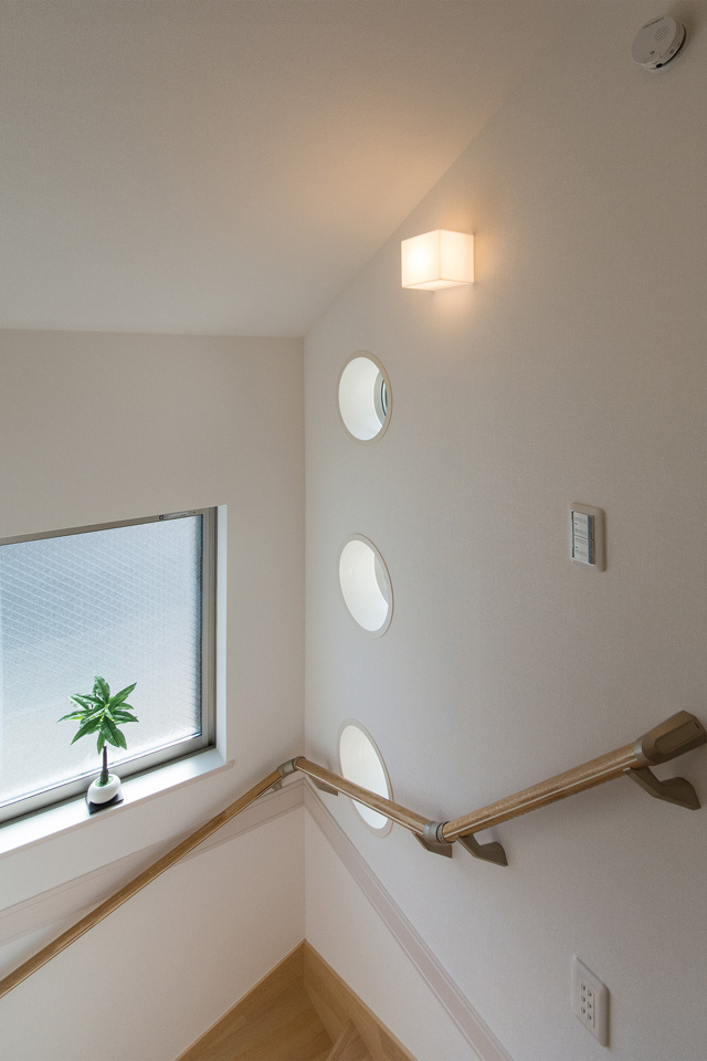 丸型のFIX窓が印象的な明るく開放感のある階段スペース。