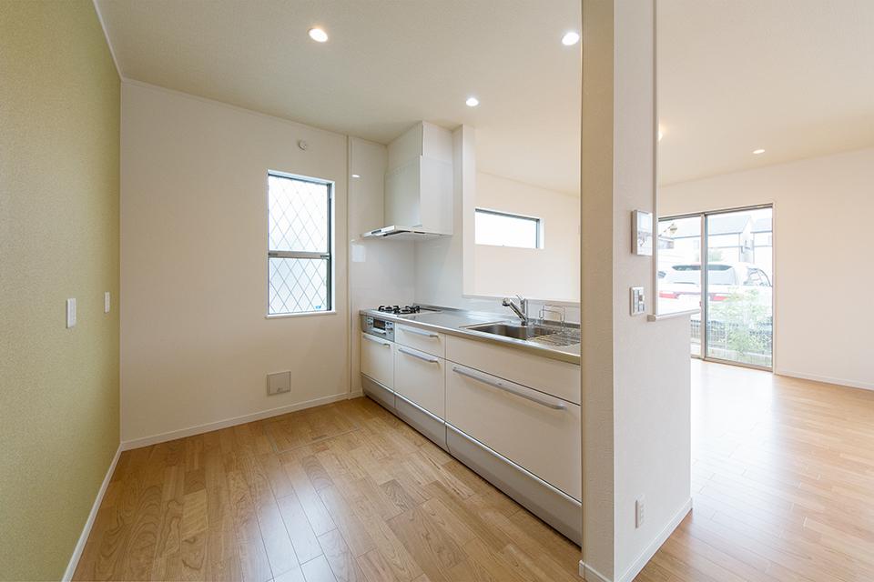 白を基調とした清潔感のあるキッチンスペース。背面にあしらったグリーンのアクセントクロスが爽やかな印象をプラスします。