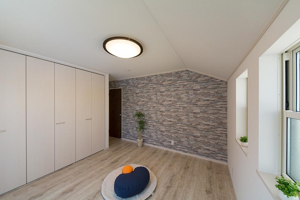 石目調のアクセントクロスがナチュラルな空間を演出する2階洋室。