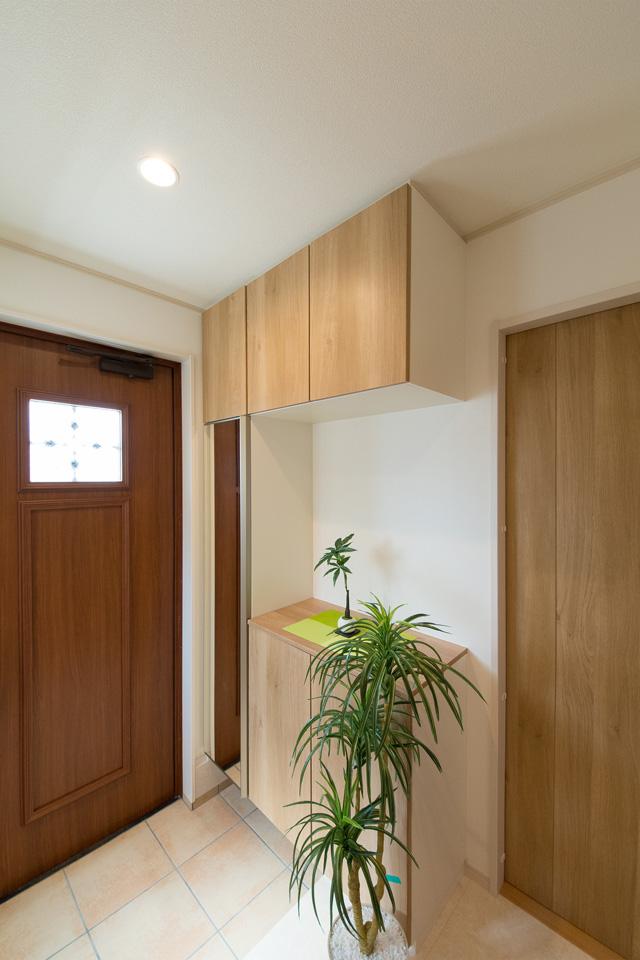 ナチュラルな雰囲気を演出するアーモンドウォルナットの玄関ドア。