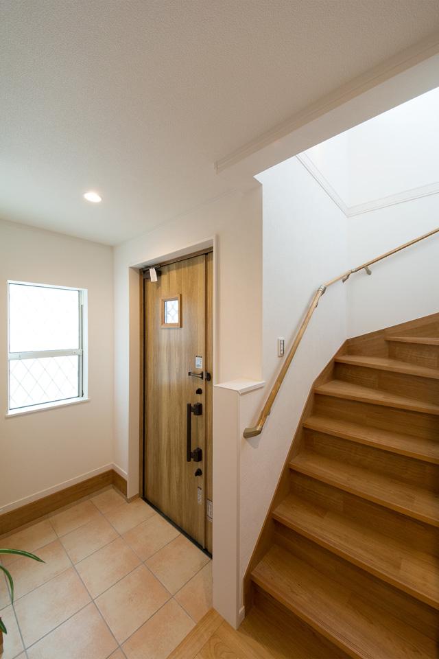 ナチュラルな雰囲気を演出するオーク色の玄関ドア。小窓部分から差し込む光が、明るく開放的ある空間を演出。