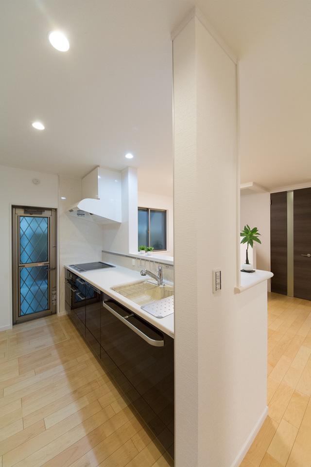 白を基調とした清潔感あるキッチン。ダークグロッシーのキッチン扉がエレガントな雰囲気を演出。