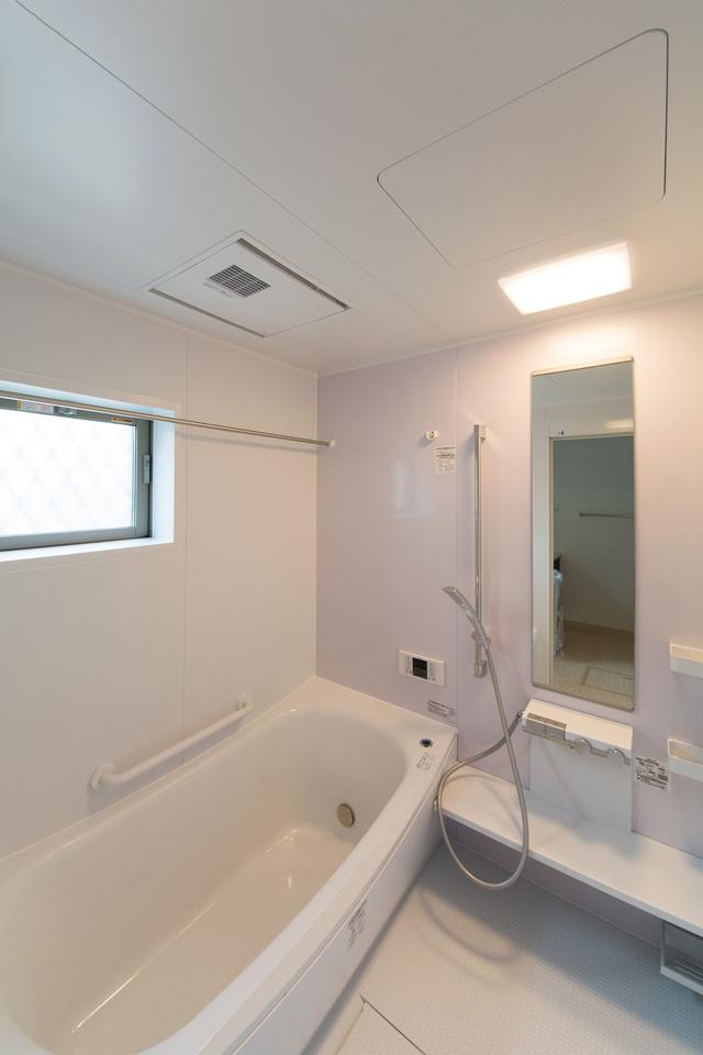 バスルーム。ライトピンクのアクセントパネルが爽やかな空間を演出。
