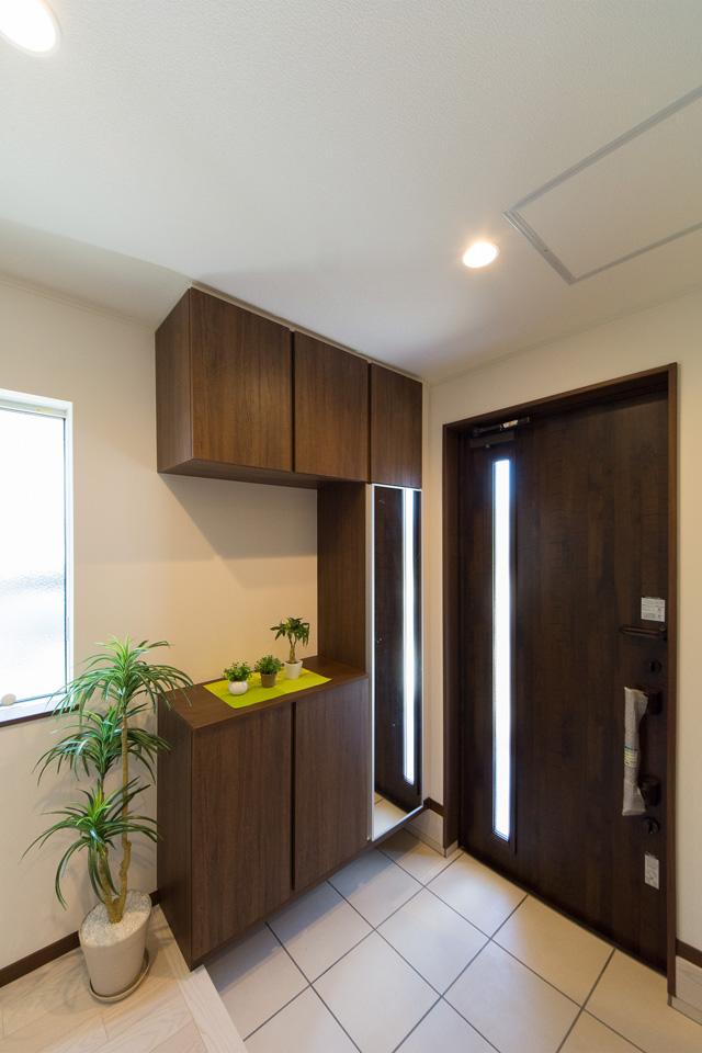 縦スリットから自然の光が差し込み明るく開放感のある玄関。