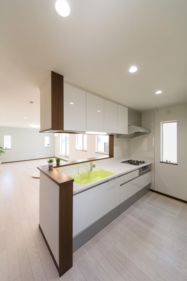 白を基調とした清潔感のあるキッチンスペース。ライムグリーンのシンクカラーが印象的です。