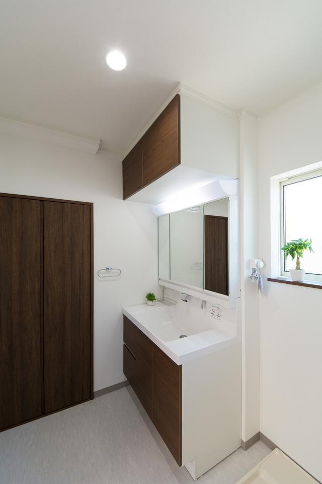 白を基調とした清潔感のあるサニタリールーム。ブラウンの洗面化粧台がナチュラルな雰囲気の空間を演出します。