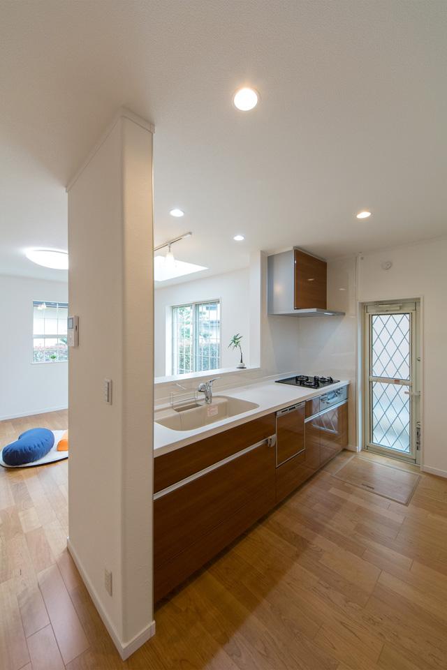 白を基調とした清潔感あるキッチン。ライトウォルナットのキッチン扉がナチュラルな雰囲気を演出。