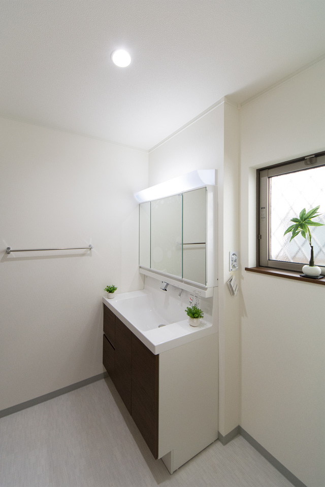 白を基調とした清潔感のあるサニタリールーム。ダークブラウンの洗面化粧台がナチュラルな印象を与えます。