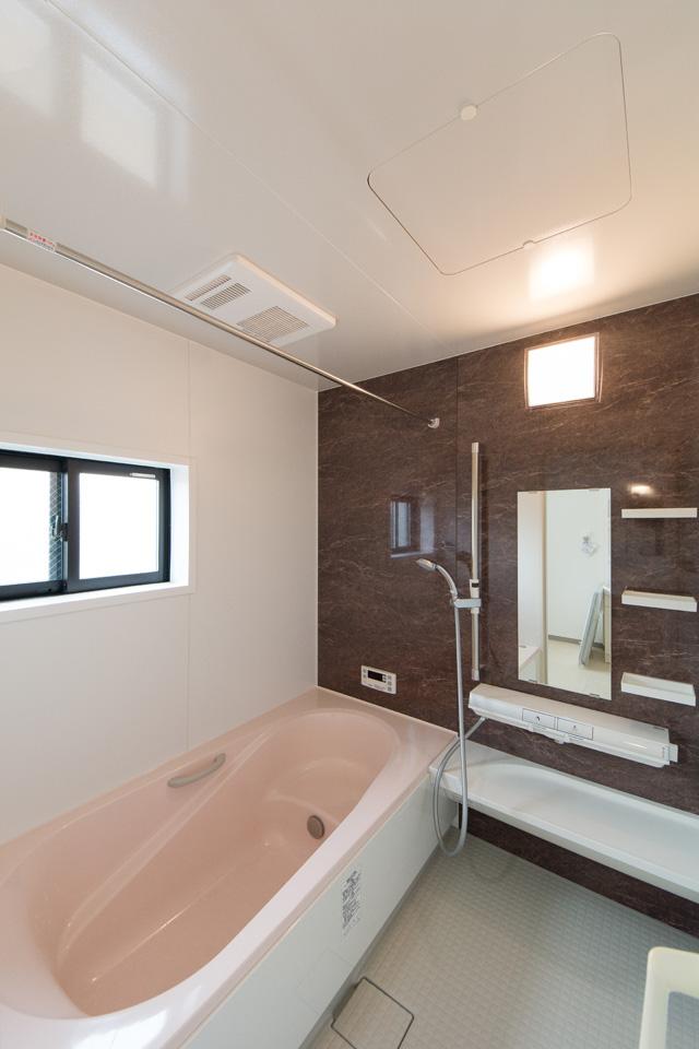 バスルーム。ナチュラルな配色のアクセントパネルを使用した、心地良い穏やかな空間。ライトピンクの浴槽が爽やかな印象をプラス。
