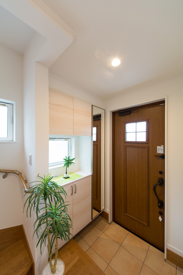 ナチュラルな雰囲気を演出するキャラメルチークの玄関ドアとベージュのテラコッタ調タイル。