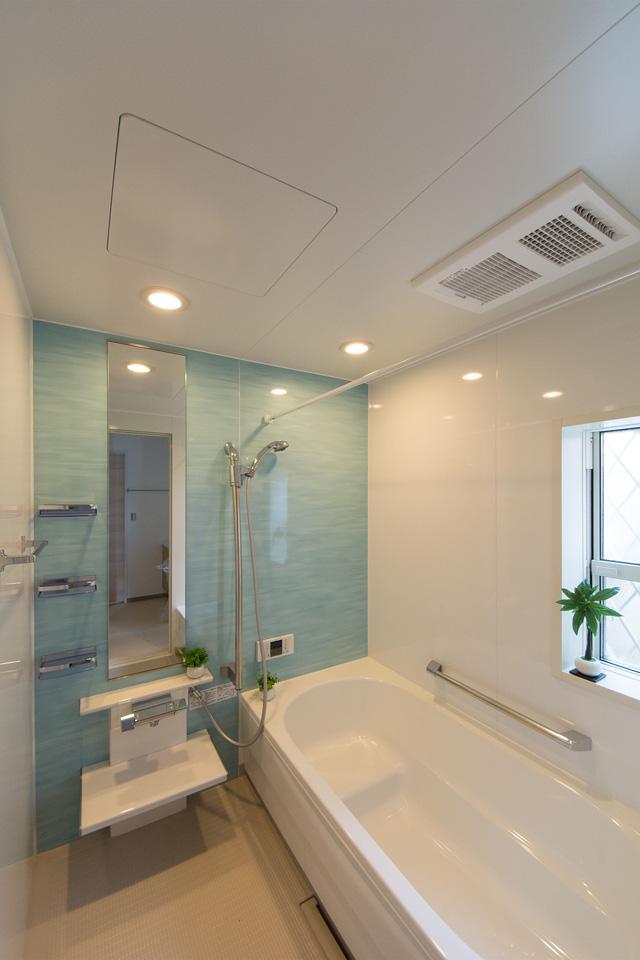 オーシャンブルーのアクセントパネルが爽やかな空間を演出するバスルーム。