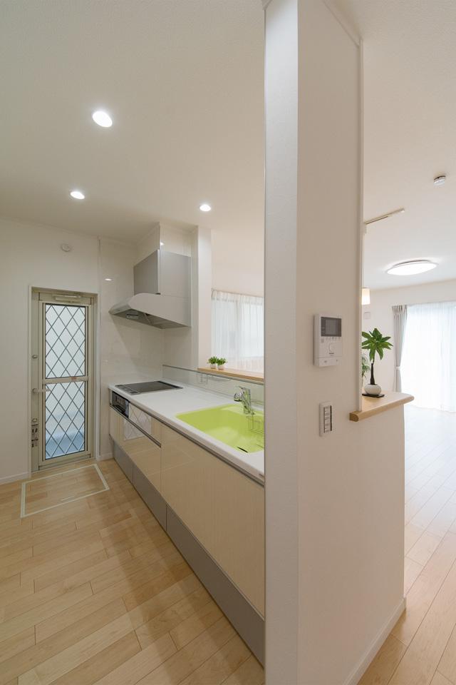 白を基調とした清潔感のあるキッチンスペース。ライムグリーンのシンクが爽やかな印象をプラス。