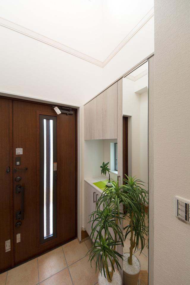 縦スリットから自然の光が差し込む、明るく開放感のある玄関。