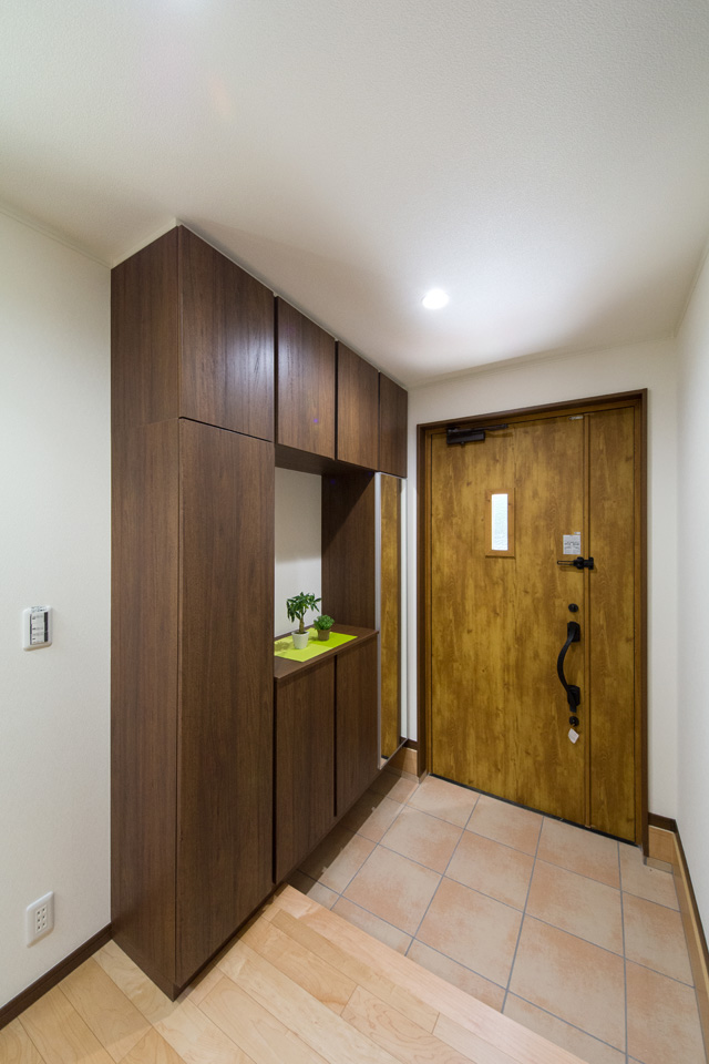 ナチュラルな雰囲気を演出するオールドパインの玄関ドアとベージュのテラコッタ調タイル。