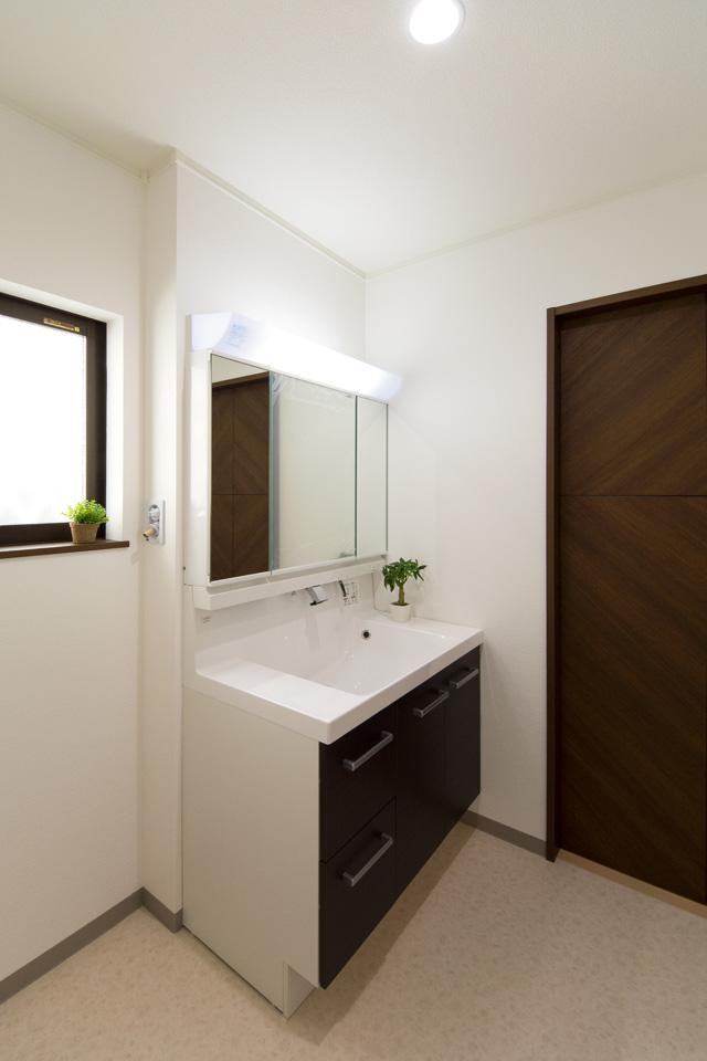 ダークブラウンの洗面化粧台がナチュラルな雰囲気の空間を演出する1階サニタリールーム。