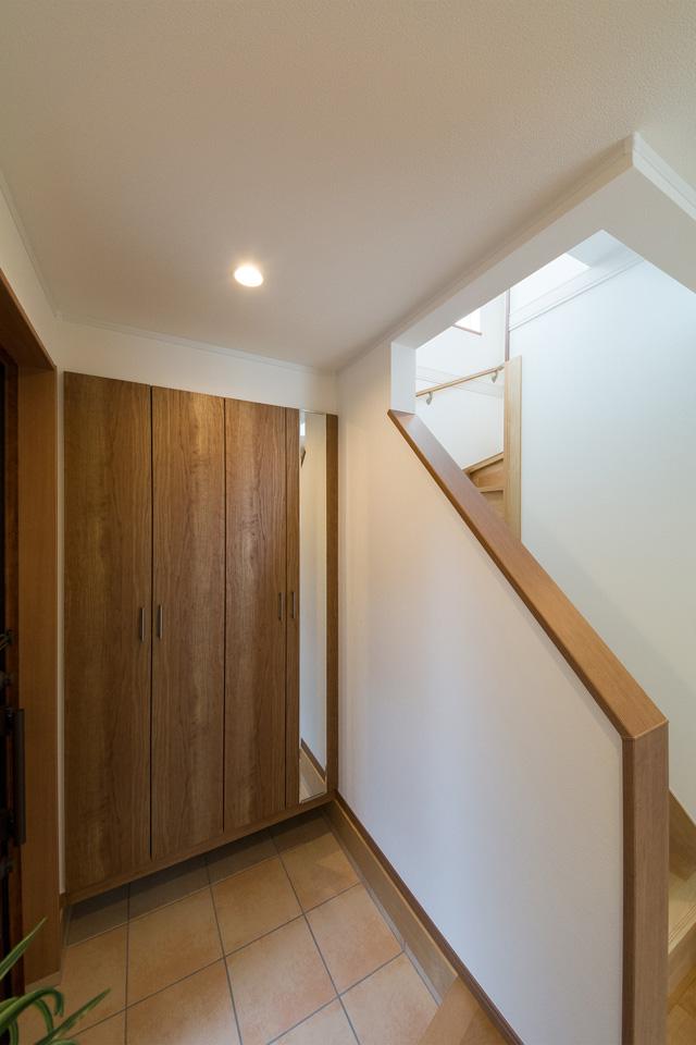 ベージュのテラコッタ調タイルとチェリー柄の玄関収納がナチュラルな空間を演出。