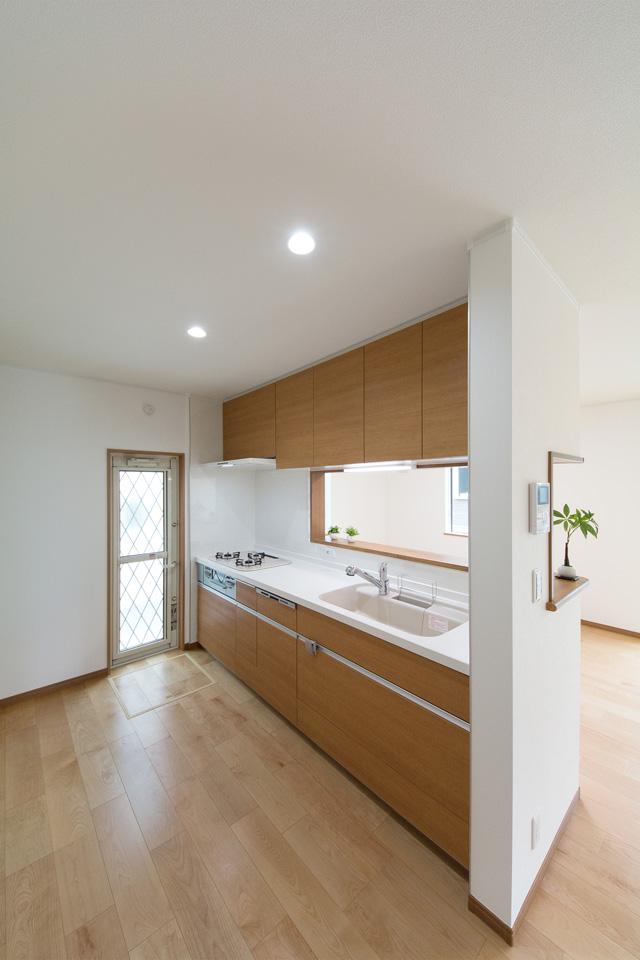 白を基調とした清潔感のあるキッチンスペース。ブラウンのキッチンパネルがナチュラルな雰囲気を演出。