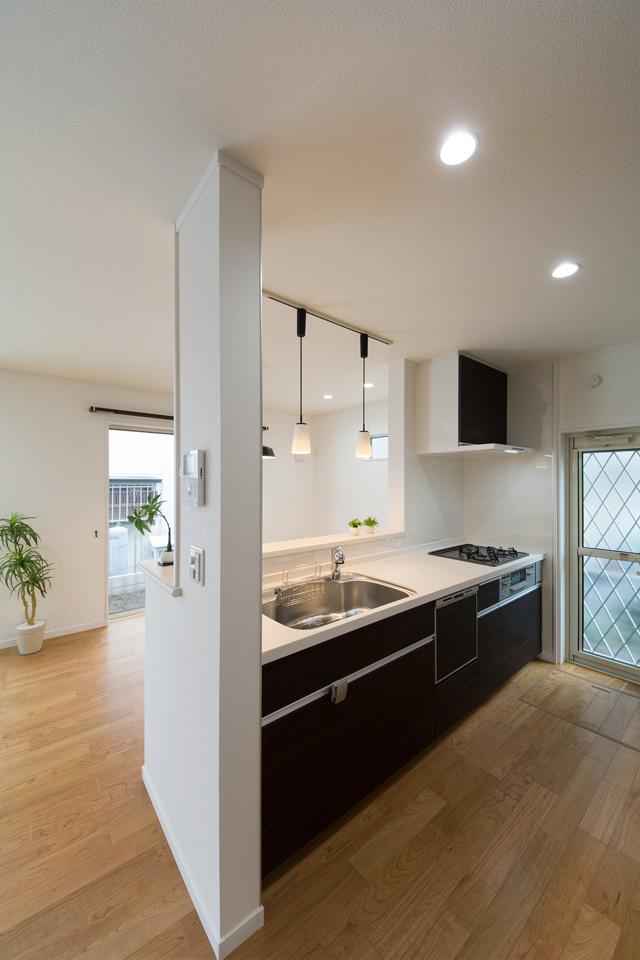 白を基調とした清潔感あるキッチン。ダークな配色のキッチン扉がエレガントな雰囲気を演出。
