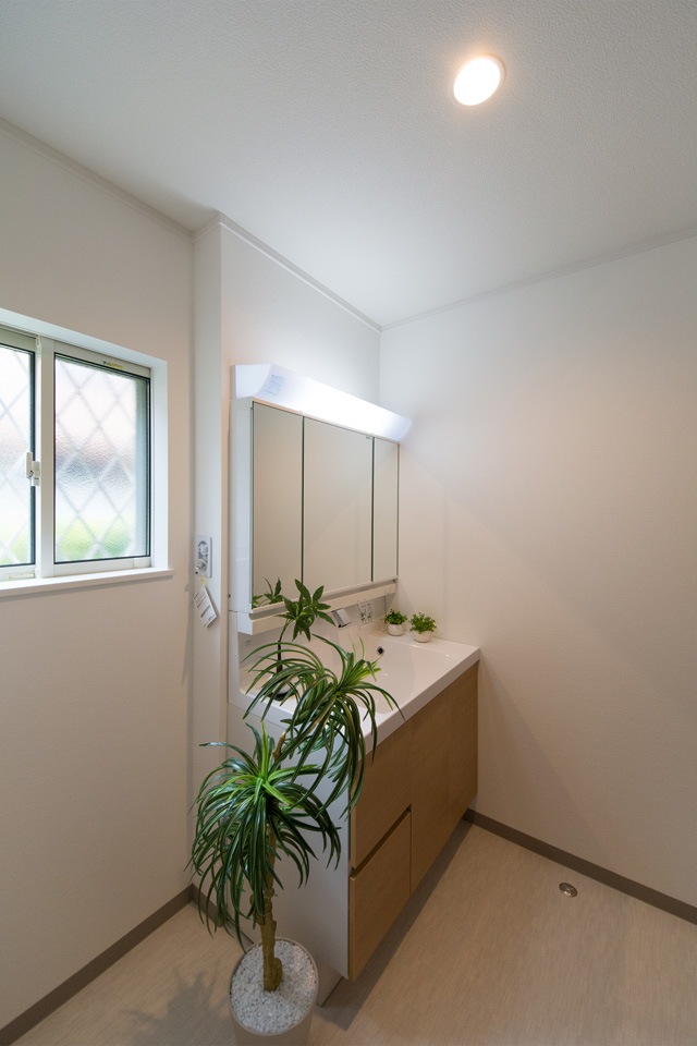 白を基調とした清潔感のあるサニタリールーム。ブラウンの洗面化粧台がナチュラルな印象を与えます。