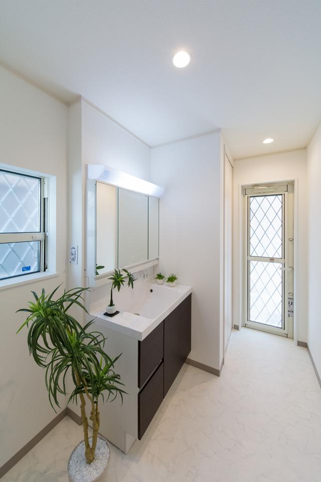ダークブラウンの洗面化粧台がナチュラルな雰囲気の空間を演出するサニタリールーム。