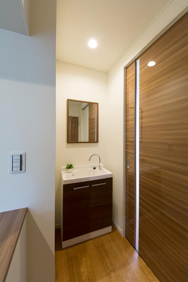 モカ色の扉がナチュラルな印象を与える玄関脇に設置した洗面化粧台。