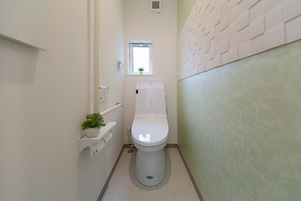白を基調とした清潔感のある1階トイレ。グリーンのアクセントクロスが爽やかな印象をプラス。