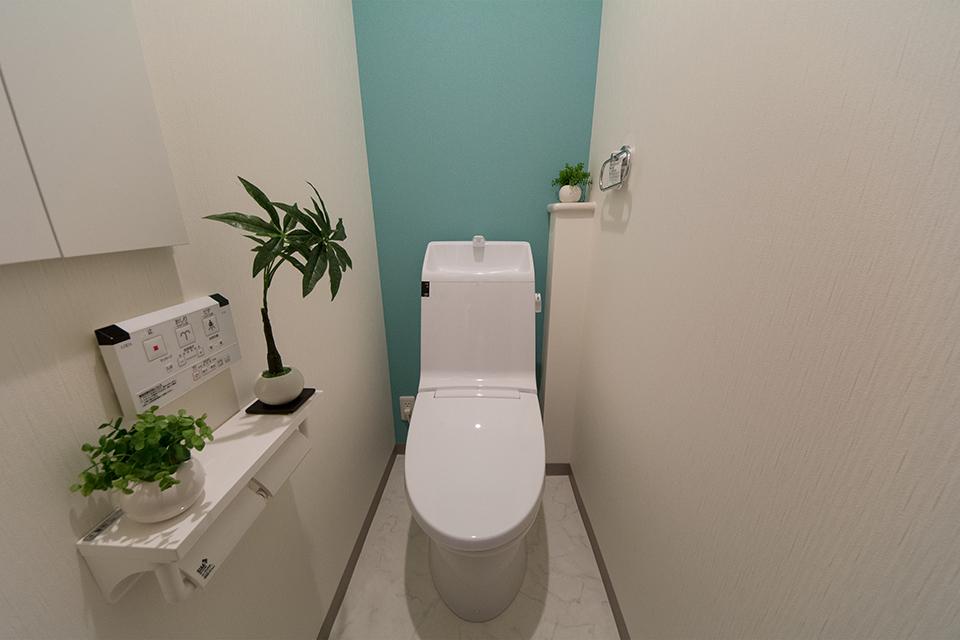 爽やかな印象を与えるターコイズブルーのアクセントクロスが印象的な2階トイレ。
