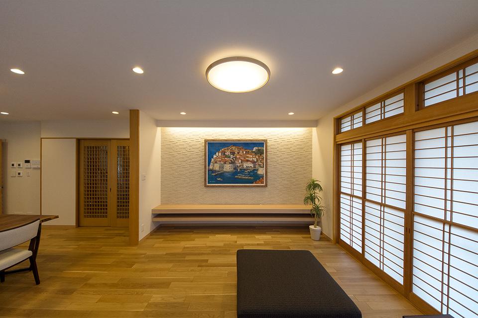 TVボードは2枚のカウンターでシンプルに。壁のエコカラットタイルは間接照明で陰影を演出します。