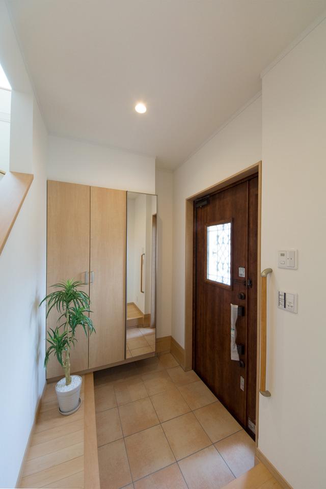 ナチュラルな雰囲気を演出するチェリーの玄関ドア。小窓部分から差し込む光が、明るく開放的ある空間を演出。
