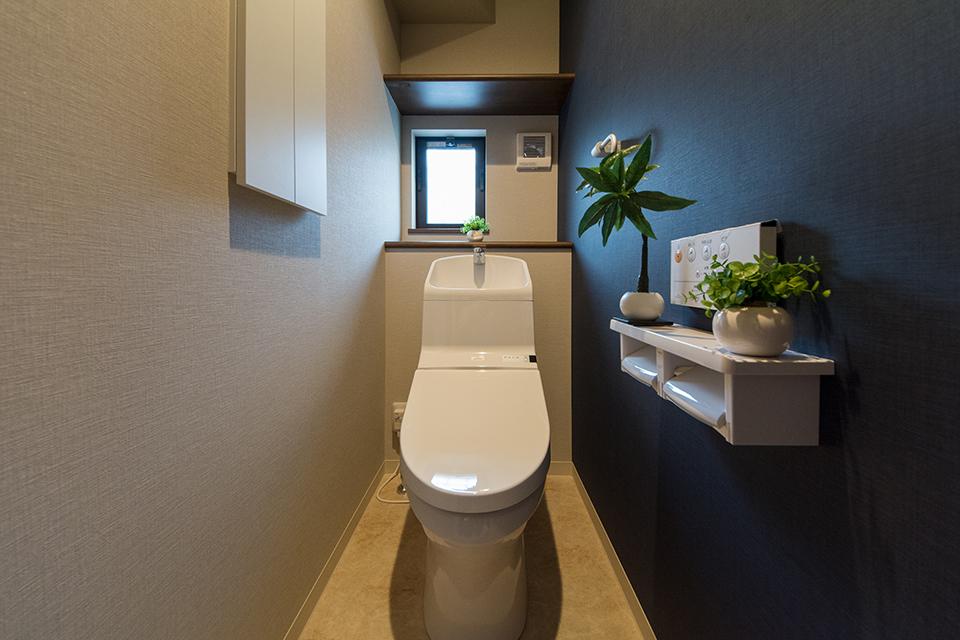 白を基調とした清潔感のある1階トイレ。ネイビーのアクセントクロスが印象的。