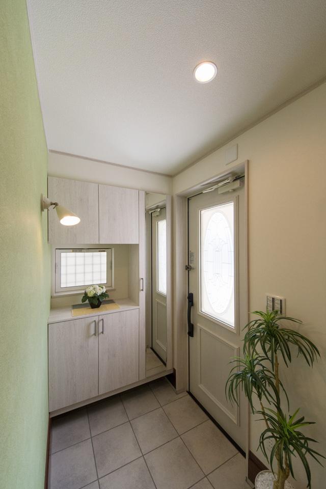 玄関ドアのガラス部分から差し込む光が、明るく開放的ある空間を演出。リーフグリーンのアクセントクロスが爽やかな印象をプラス。