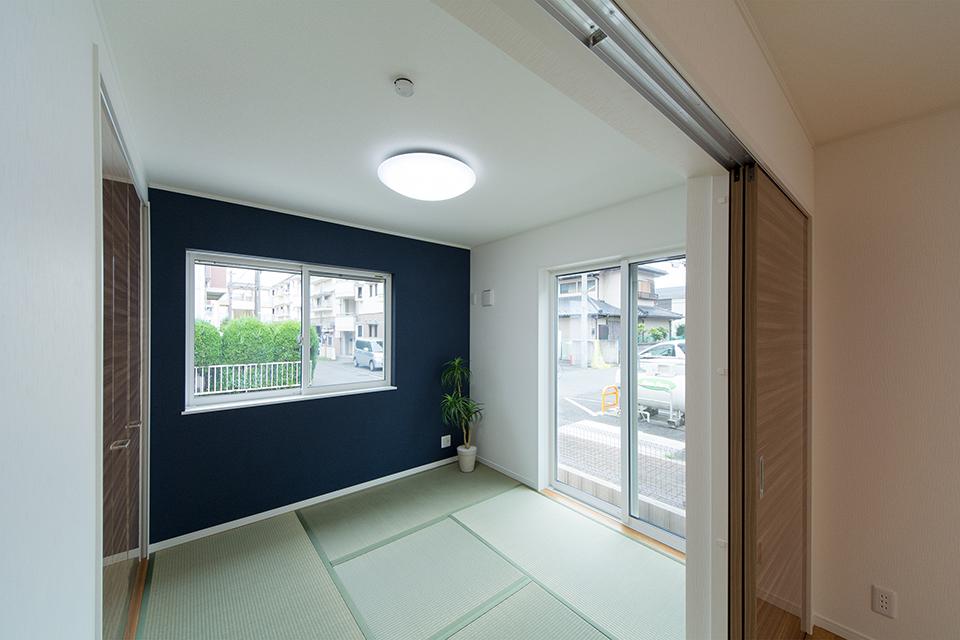 畳のさわやかなグリーンが空間を彩る1階畳敷きスペース。紺のアクセントクロスがモダンな表情をプラス。