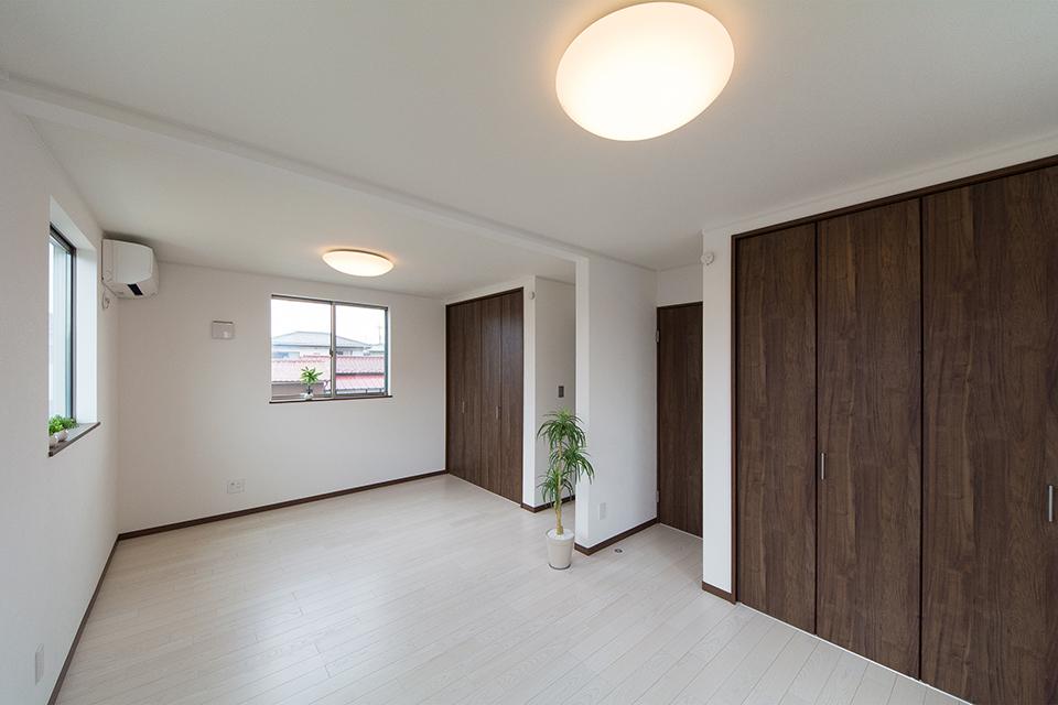 2階洋室もリビング同様の配色。ホワイトアッシュのフローリングにウォルナット調の建具がメリハリのある空間を演出。