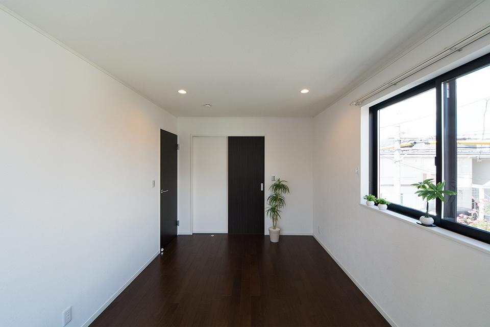 2階洋室。ブラックウォルナットのフローリングと白いクロスがメリハリのある空間を演出。