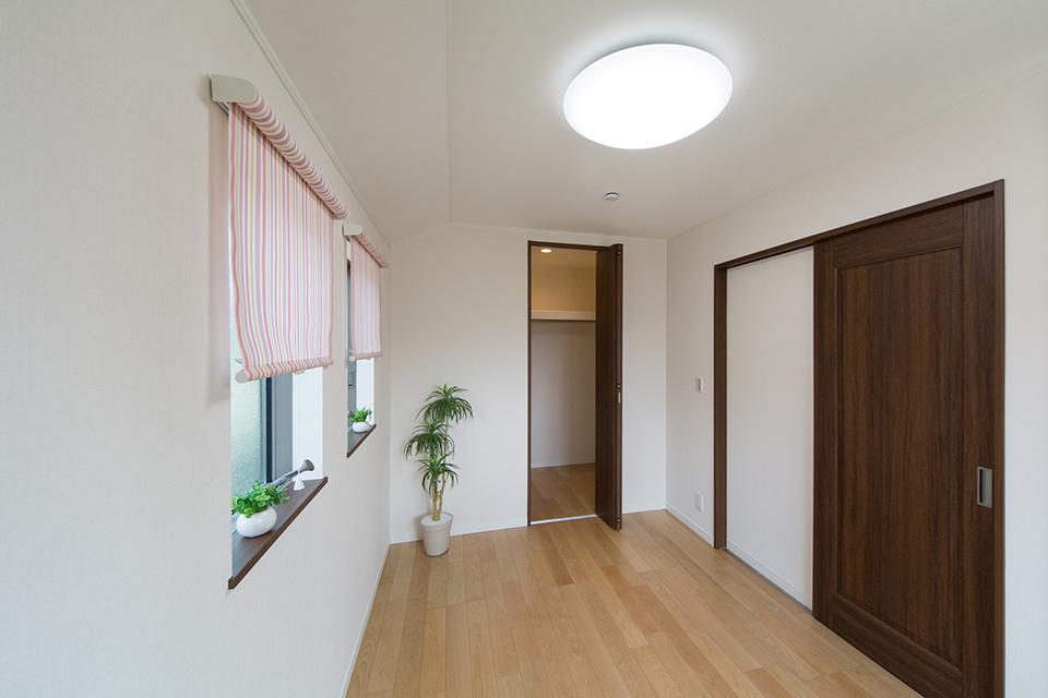 2階洋室。バーチのフローリングとウォルナット調の建具が、リビング同様ナチュラルな空間を演出。
