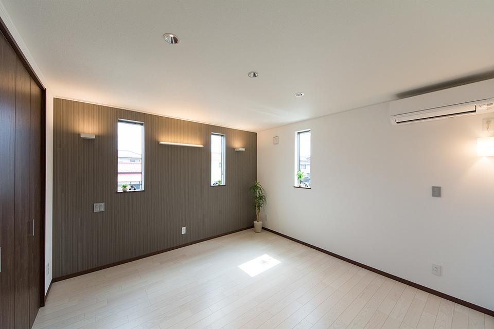ダークなアクセントクロスが空間を引き締め、スタイリッシュな印象の2階主寝室。