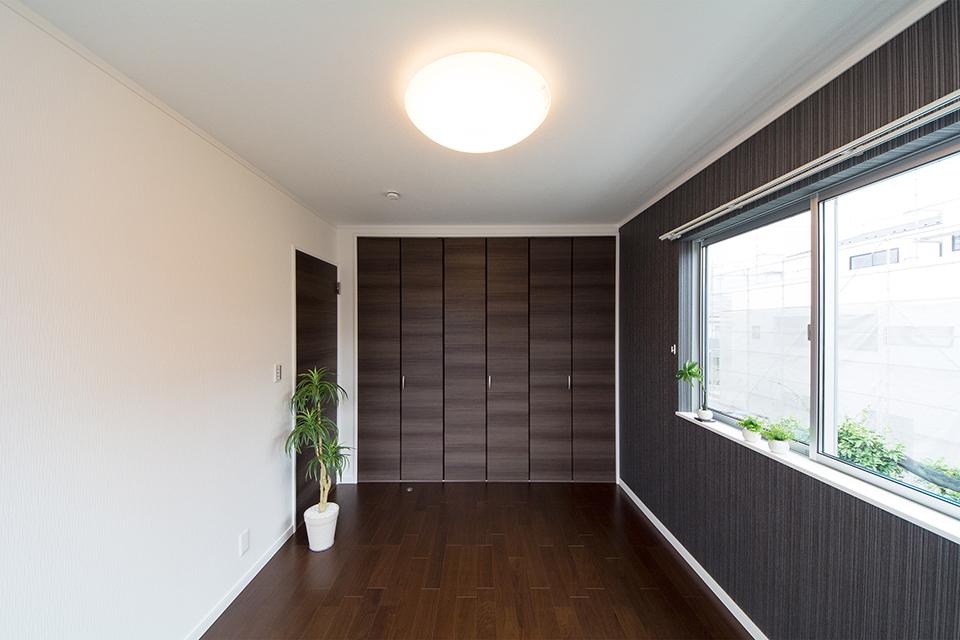 2階洋室。ブラックウォルナットのフローリングと白と黒のクロスがメリハリのあるモダンな空間を演出。