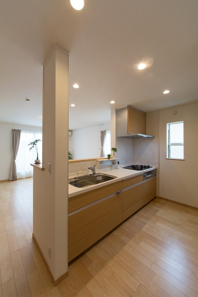 白を基調とした清潔感のある1階キッチンスペース。ブラウンのキッチンパネルがナチュラルな雰囲気を演出。